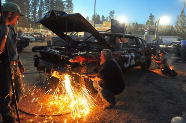 Brian Holt of Ceres, California (center) and crew members use acetylene torches to cut excess metal from the fenders of his No. 31 Undertaker car in the pits of the Nevada County Fairgrounds arena during Sunday night's destruction derby.