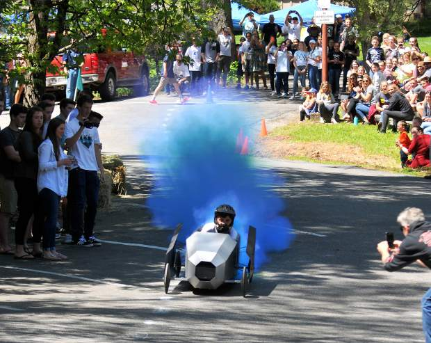 Forest Lake Christian eighth grader Brady Steffenson, draws the attention of the crowd as blue smoke comes out of his team's TIE fighter inspired derby car during the school's second annual Forest Lake Christian School Junior High Soap Box Derby held Friday afternoon. The event was the culmination of a Spring project for the 7th and 8th grade Science classes and showcased the student's creativity as well. Eight individual teams competed against each other in different categories which included longest distance, fastest, and creative desgin. Students, siblings, parents and grandparents came from all around to watch it.