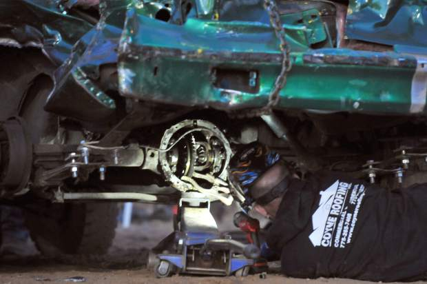 Destruction derby pit crew members weld rear differential gears together for added traction in the arena.
