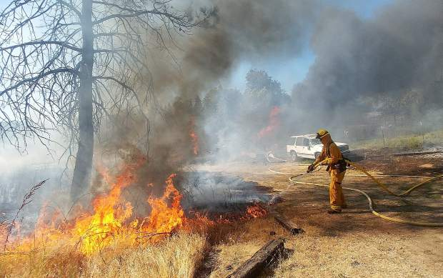 A firefighter places water on a portion of the Pleasant Fire Wednesday afternoon near the fire's origin behind Peterson's Corner.