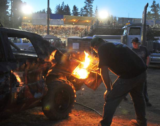 A member of the Undertaker's pit crew works on removing rear fenders with an acetylene torch between heats at the Nevada County Fair Sunday night.