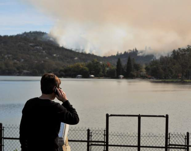 An evacuated resident of Lake Wildwood makes phone calls as the Lobo Fire burns across the lake Monday morning from the Lake Wildwood dam.