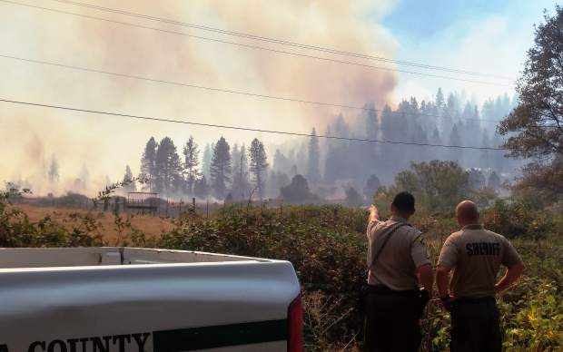 A pair of Nevada County Sheriffs deputies assess an advancing front of the Lobo Fire Monday afternoon as the blaze grew to over 900 acres by Monday evening.