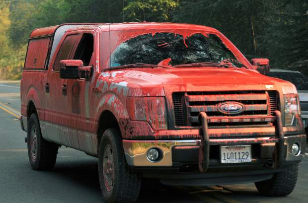 A Penn Valley Fire vehicle makes its way along Bitney Springs Road covered in fire retardant, dropped from an aircraft overhead.