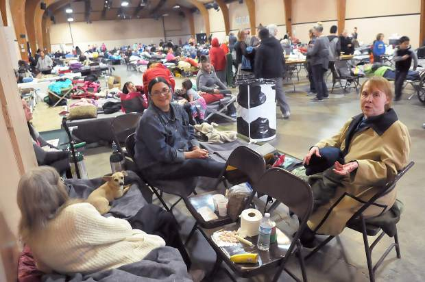 Marysville's Donna Keeling (from right), Linda Iturriza, and Oroville's Eilene Pawlec, sit on chairs and cots while they await an update on the Oroville Dam evacuations Monday morning at the Nevada County fairgrounds.