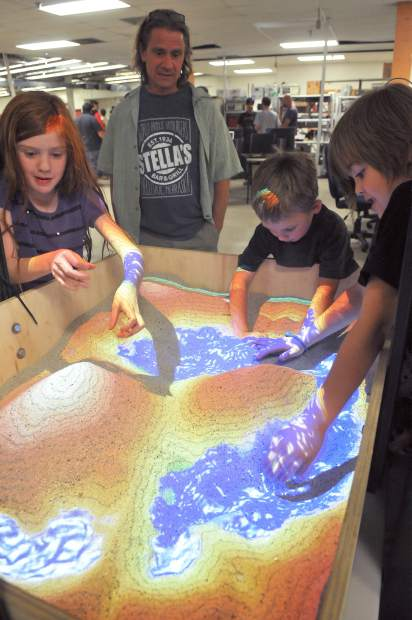 Youth in attendance of Thursday's open house of the Curious Forge's new digs off of Bitney Springs Road, inspect a augmented reality sand box created by Curious Forge members.