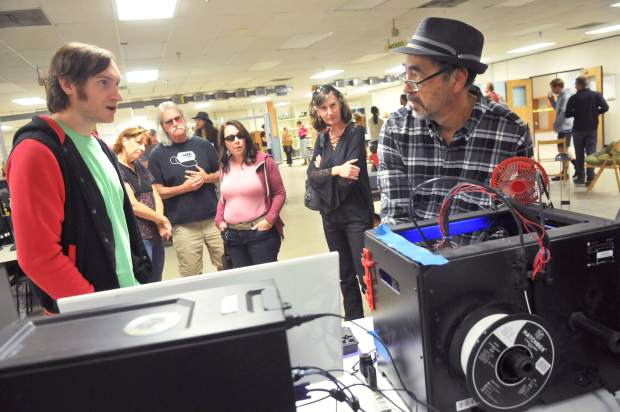 Curious Forge members explain how tools such as the 3-D printner work during Thursday's open house.