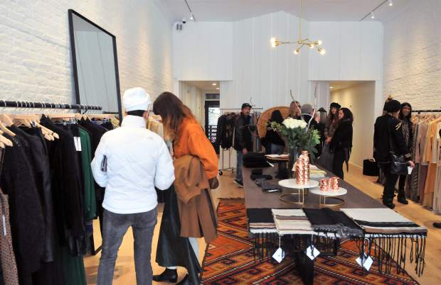 Customers check out the selection of apparel at Luxe Nomad following Thursday's ribbon cutting ceremony.