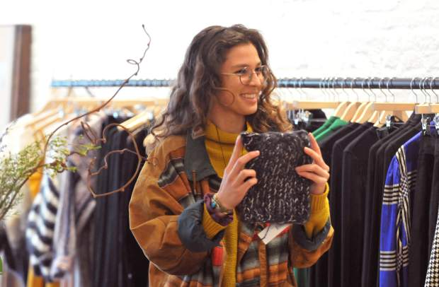 Grass Valley's Alejandra Falcon smiles as she shows off an article of clothing that she likes inside of Nevada City's newest clothing and apparel store, Luxe Nomad.