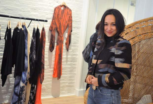 Isis Indriya smiles as she tries on a piece of apparel Thursday at Luxe Nomad in downtown Nevada City.