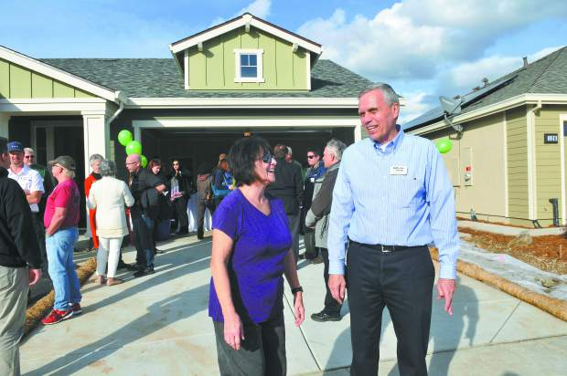Towne Homes' Ed Meadows and new Towne Home homeowner Vicki Marque, smile in front of one of the Ridge Meadows homes that has just been completed in Grass Valley.