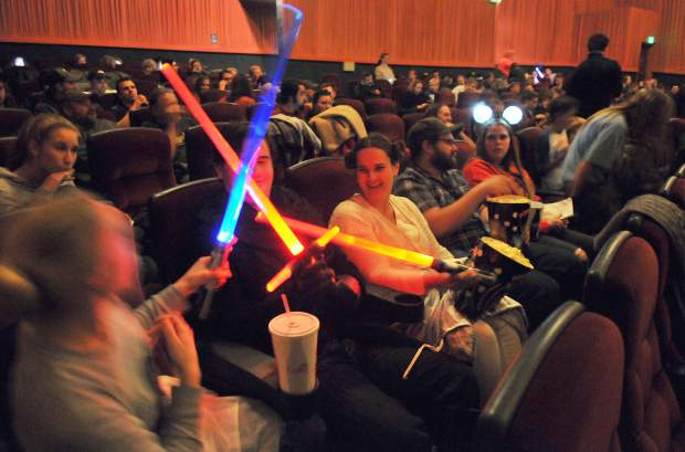 Members of the Hedenland family play with their light sabers in the seats of the Del Oro Theater while waiting for the first sold out screening of The Last Jedi to begin.