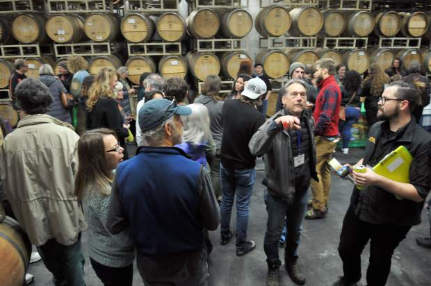 Nevada City Film Festival opening event attendees sip on wine and munch on snacks in the barrel room of Nevada City Winery Friday night.