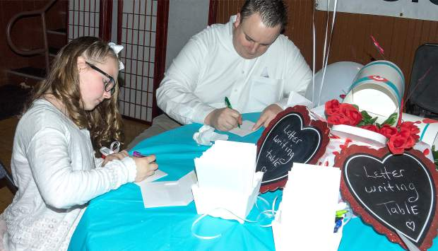 Audrey Larios, 10, and father Mike Larios write love letters to each other Saturday evening at the 11th annual Daddy Daughter Dance hosted by Community Beyond Violence.