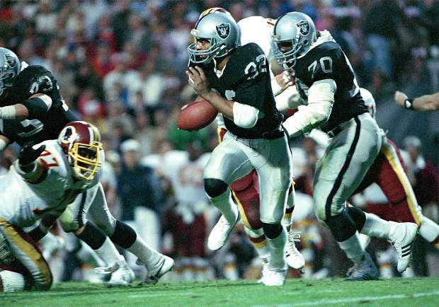 Marcus Allen (32) of the then Los Angeles Raiders runs with the ball as teammate Henry Lawrence (70) blocks a Washington Redskins defender during Super Bowl XVIII action at Tampa Stadium in Tampa, Fla., Jan. 23, 1984. Allen scored two touchdowns in the game and was named Most Valuable Player. The Raiders won 38-9.