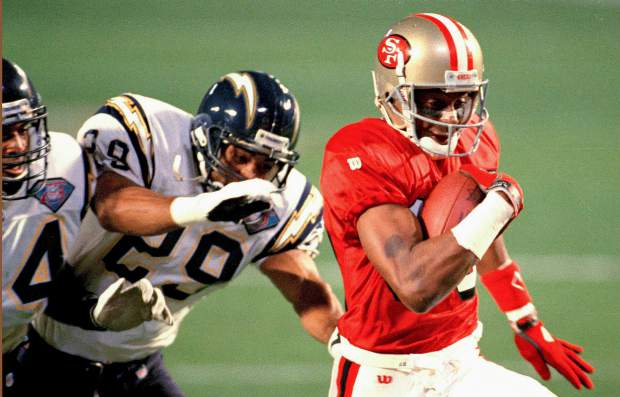 San Francisco 49ers wide receiver Jerry Rice is chased by San Diego Chargers' Darren Carrington (29) and Stanley Richard (24) on his way to a touchdown during NFL football's Super Bowl XXIX at Joe Robbie Stadium in Miami. Rice established career records for receptions, yards, and touchdowns in a Super Bowl.