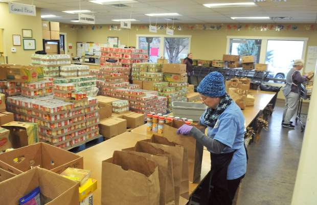 A volunteer helps sort food Thursday morning inside of Interfaith Food Ministry off of Henderson Street in Grass Valley.