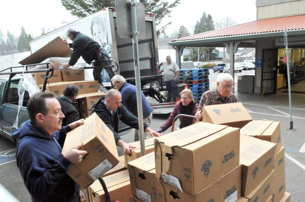 Volunteers help unload a pallet of chicken donated from SPD Market, Thursday morning at Interfaith Food Ministry.