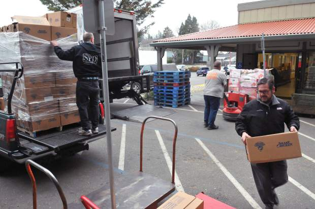Bob Boggeri of Smart Chicken, at right, helps unload a pallet of his company's chicken, that has been donated from SPD Market, to Interfaith Food Ministry in Grass Valley.