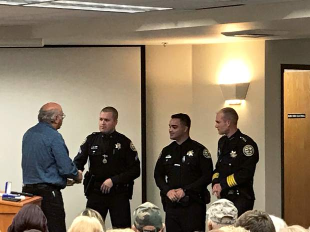 Grass Valley Mayor Howard Levine shakes hands with Corporal Jesse Cloyd and Officer Mel Bird of the Grass Valley Police department, who were honored by Chief Alex Gammelgard Tuesday night with a life saving award.