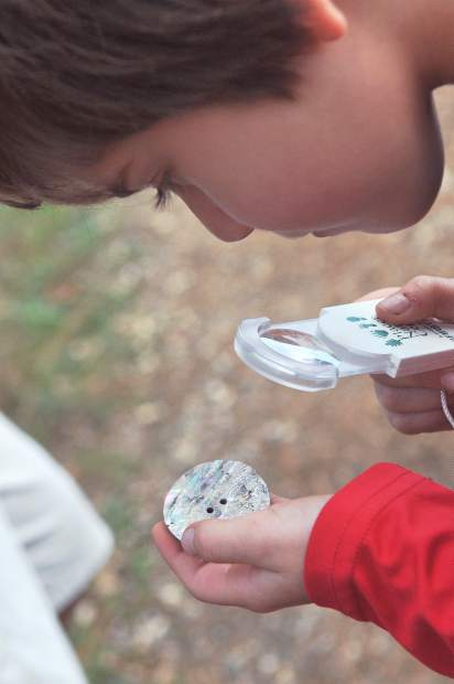 Harrison Adams uses a magnifying glass to inspect the sheen of an abalone shell shown to represent what the native people's of the area used in the region, during Saturday's junior conservationist hike along Grass Valley's Litton Trail.