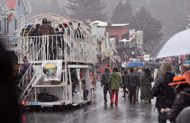 Members of the Nevada County Alliance walk through the rain as they pick up the rear of the parade floats during Sunday's Mardi Gras parade.