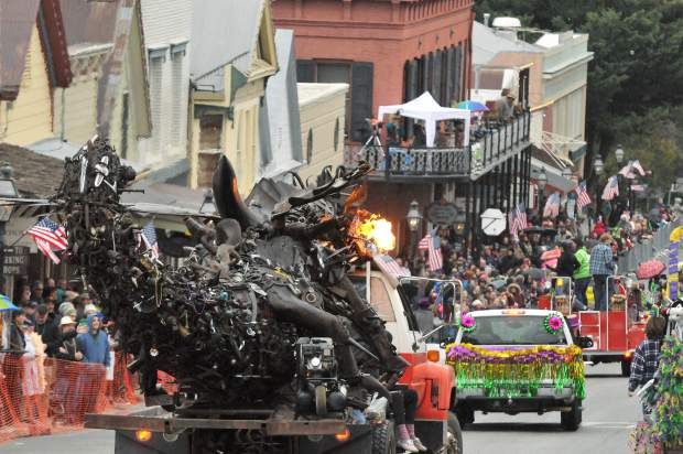 A fire breathing metal sculpture in the shape of a dragon, rolls down Broad Street atop a tow truck prior to Sunday's rain and hail storm during the annual Nevada City Mardi Gras Parade.
