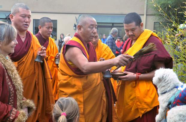 The monks use a peacocks feather, water, and a chant to administer the blessing for prosperity, healing, and happiness upon the animals.