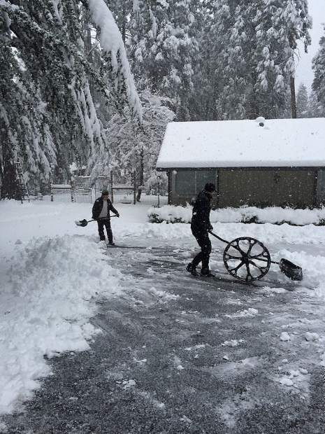Local residents clearing the driveway of almost a foot of snow Monday morning.