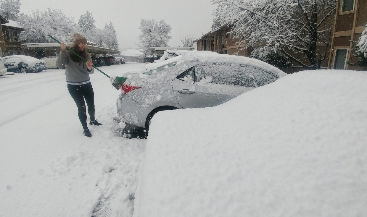 Grass Valleys Sarah Cassidy uses a broom to wipe an accumulation of snow from her vehicle Monday morning at the Oakridge apartments in Grass Valley. While Cassidy works from home and didn't need to leave, she and a friend were on a mission for coffee. Others in Nevada County weren't as fortunate, getting stuck in traffic, under utility poles, or in a vehicle pileup that occurred in front of Lyman Gilmore School.