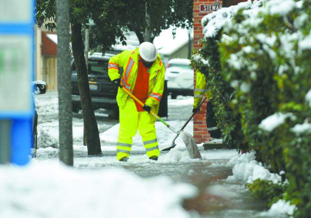 Utility workers use shovels to clear snow from the doors of City Hall Monday morning in Grass Valley. Utility workers across the Sierra were busy clearing up traffic snarls which included a pile up in front of Lyman Gilmore School, and multiple utility lines down, in one instance trapping a family inside until first responders could rescue them near La Barr Meadows Rd.