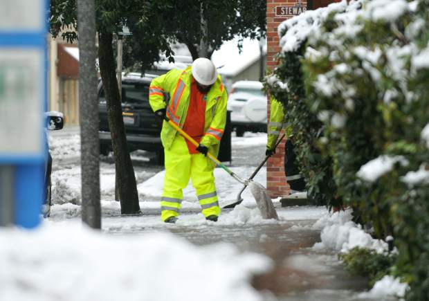Utility workers use shovels to clear snow from the doors of City Hall Monday morning in Grass Valley. Utility workers across the Sierra were busy clearing up traffic snarls, which included a pileup in front of Lyman Gilmore School, and multiple utility lines down, in one instance trapping a family inside until first responders could rescue them near La Barr Meadows Road.