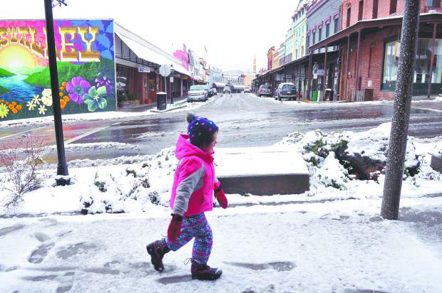 Five year old Maggie Poston walks in the foot prints of her father Dan, made in the snow on the sidewalk along Main Street in downtown Grass Valley Monday morning. Early morning snowfall caused numerous headaches for Nevada County drivers, and peaceful moments for pedestrians.