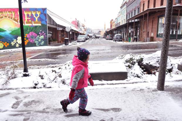 Five-year-old Maggie Poston walks in the footprints of her father Dan, made in the snow along Main Street in downtown Grass Valley Monday morning. Early morning snowfall caused numerous headaches for Nevada County drivers, and peaceful moments for pedestrians.