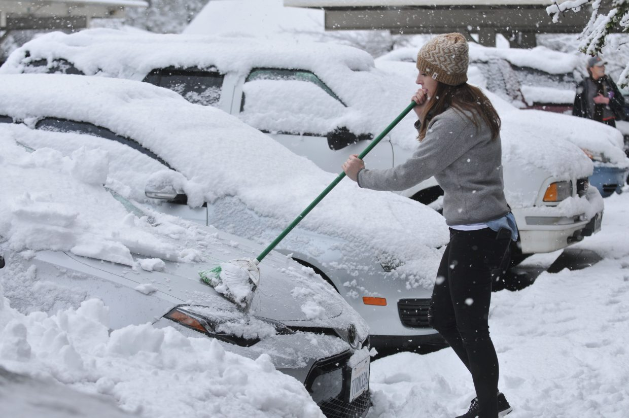 Grass Valley's Sarah Cassidy uses a broom to sweep snow from her vehicle Monday morning at the Oak Ridge Apartments in Grass Valley. While Cassidy works from home and didn't need to leave the house in the morning, she did have a mission to get a hot cup of coffee.