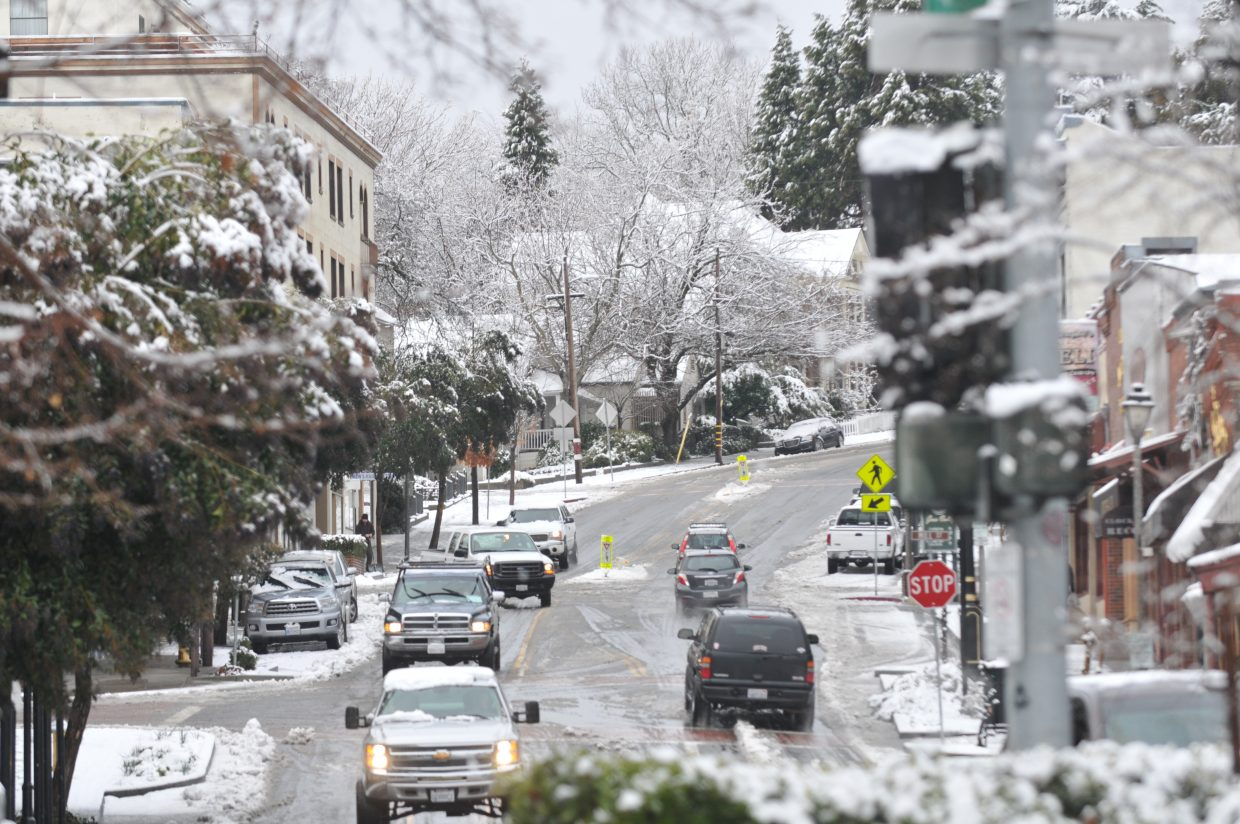 Drivers navigate Main at Mill Streets in downtown Grass Valley following Monday morning's snow showers which dropped between 6 and 12 inches of snow in places.