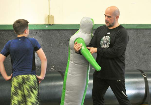 Lyman Gilmore wrestling coach Tony Guerra, goes over technique with his wrestlers at a practice earlier this month.