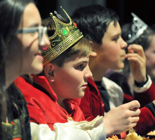 Medieval Feast royalty watch the entertainment unfold before them, including sword fighting, a magician, and a madrigal choir.