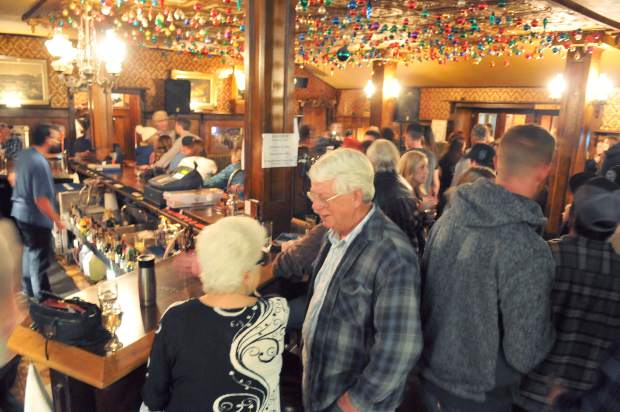 Patrons of the National Hotel greet one another Saturday night in the hotel's bar, the last night of operation before transferring ownership.