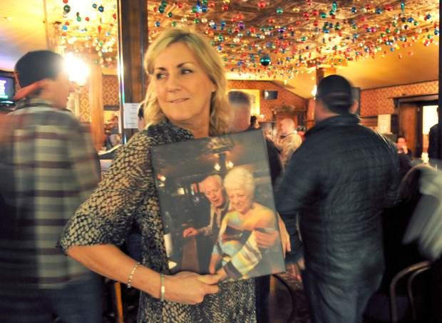 Photographer Debbie Moody holds a photograph of the National's longtime owners during Saturday night's sendoff gathering in the hotel's bar. Moody had many fond memories of working in the bar for many years.