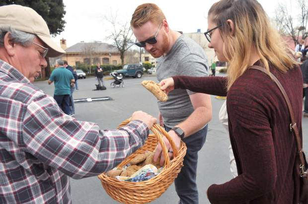 Brother and sister Bennett Smithhart and Suzie Hood pick an official dog food filled pasty from the basket of Joe Hagler, whose wife Carol Kinyon makes them specially for the pasty olympics. Kinyon soaks the dog food in beef liver oil, which is added to the flour used to make the pasties, making them especially desirable for the four-legged kind.