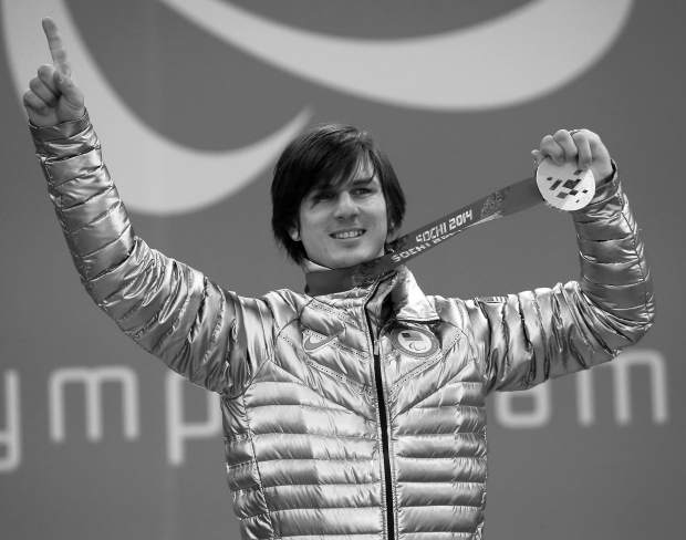 Evan Strong, of United States, winner of the men's para snowboard cross, standing event, celebrates during a medal ceremony at the 2014 Winter Paralympic, Friday, March 14, 2014, in Krasnaya Polyana, Russia. (AP Photo/Dmitry Lovetsky)
