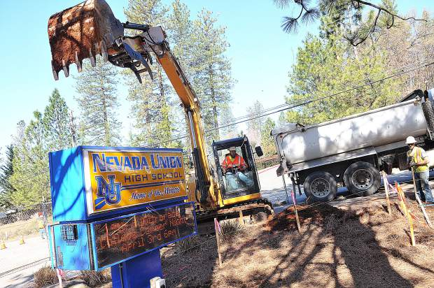 Hansen Brothers Enterprises construction workers use an excavator to help pave a new path along Ridge Road in front of Nevada Union High School that will be used as a pedestrian walkway. Nevada County schools are utilizing Measure B funds while students are away at spring break, though construction will continue into the school year.