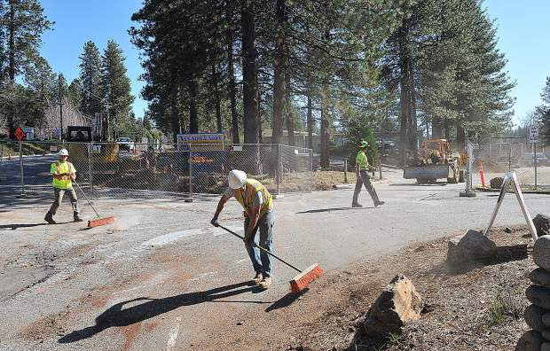 Construction workers use push brooms to clear the driveway of Nevada Union High School Wednesday morning after dropping a handful of the 30 trees removed as part of the Measure B construction going on during spring break. Construction will continue into the remainder of the school year and the main parking lot will remain closed. A second phase of Measure B construction at Nevada Union High School will begin following the last day of school in June.