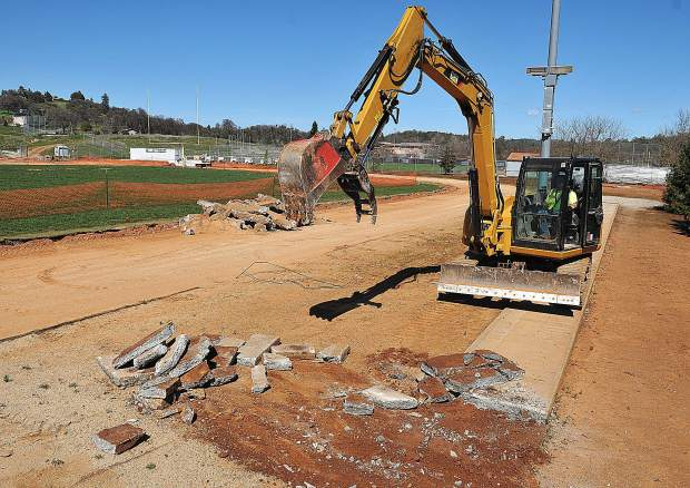 A Lamon Construction Company excavator is used to pull up the concrete long jump runway adjacent to the Bear River track and field Wednesday. The construction company has been authorized to use Measure B funds to upgrade the track.
