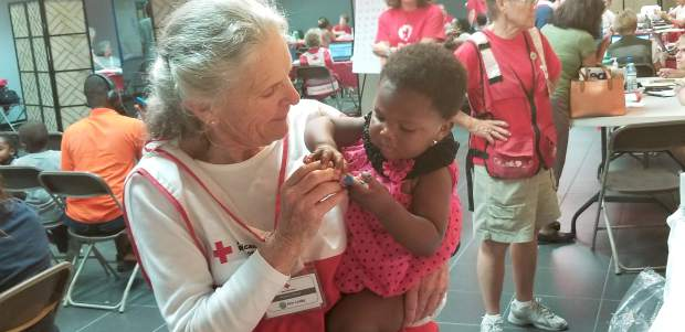 "Humanitarian and psychologist Annie Looby volunteers with the American Red Cross Disaster Mental Health team, helping disaster victims put their lives back together. ""Holding babies is one of my things,"" she said."
