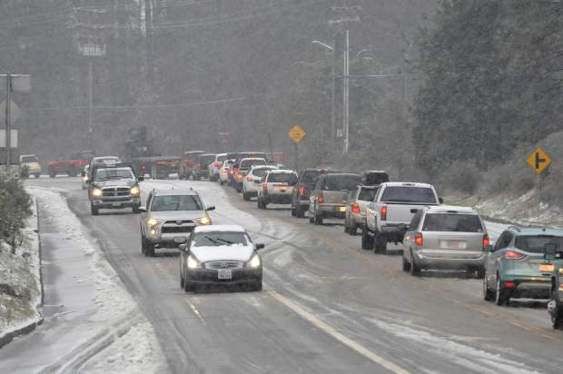 Vehicles slowly drive down the Brunswick Rd. hill Friday afternoon as uphill traffic backs up in the snowfall.