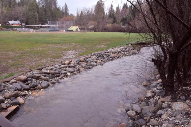 Little Deer Creek flows swiftly, but within its banks, Friday through a portion of creek bed re-engineered to keep Pioneer Park from flooding in Nevada City.