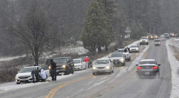 Motorists tie up traffic while installing tire cables along Brunswick Rd at Idaho-Maryland Rd. Friday afternoon. The CHP advised for temporary closure of the roadway following multiple spin outs and a school bus collision.