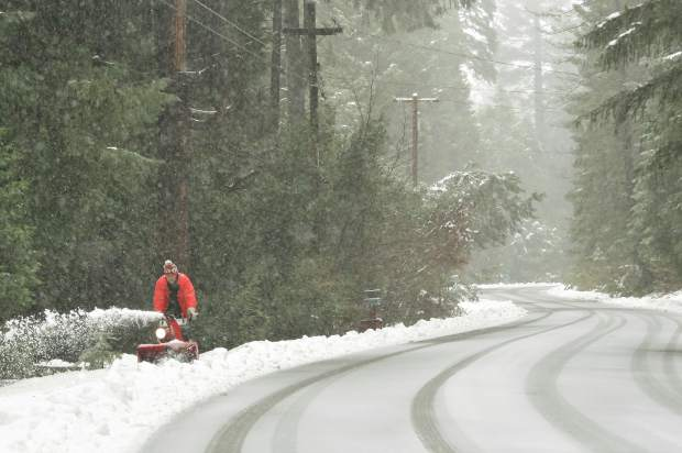 Cascade Shores resident Ron Breeden uses a snow blower to keep snow from piling up in front of his residence off of Pasquale Rd. Friday afternoon.